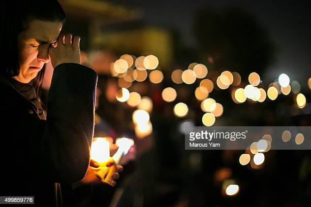 Community members gather during a candlelight vigil to honor the victims of the mass shootings at the Inland Regional Center December 3 2015 at San...