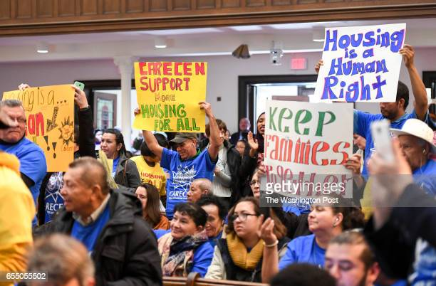 Community members hold signs as Mayor Muriel Bowser speaks at the More For Housing Now rally at the Foundry United Methodist Church in Washington DC...
