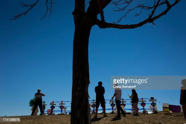 Community members lay roses by 12 crosses erected near the Aurora Municipal Building July 20 2013 in Aurora Colorado The ceremony marks the one...