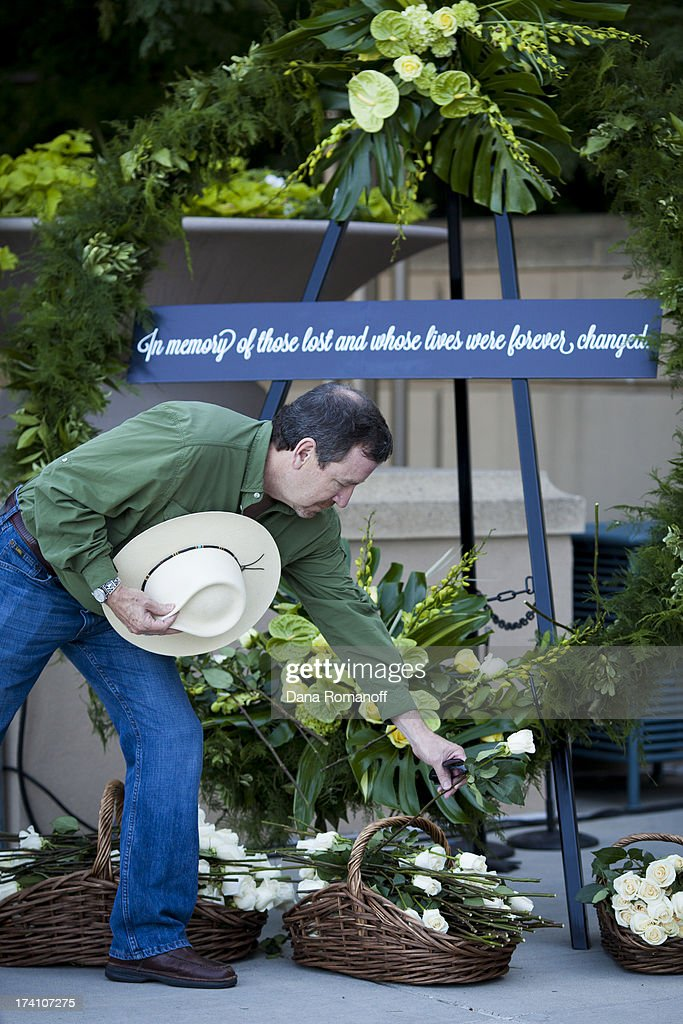 Community members lay white roses on a wreath at a remembrance ceremony July 20, 2013 in Aurora, Colorado. The ceremony marks the one one-year anniversary of the Aurora Movie Theatre Shootings in which James Holmes killed 12 people and injured more than 50 during a mass shooting in 2012.