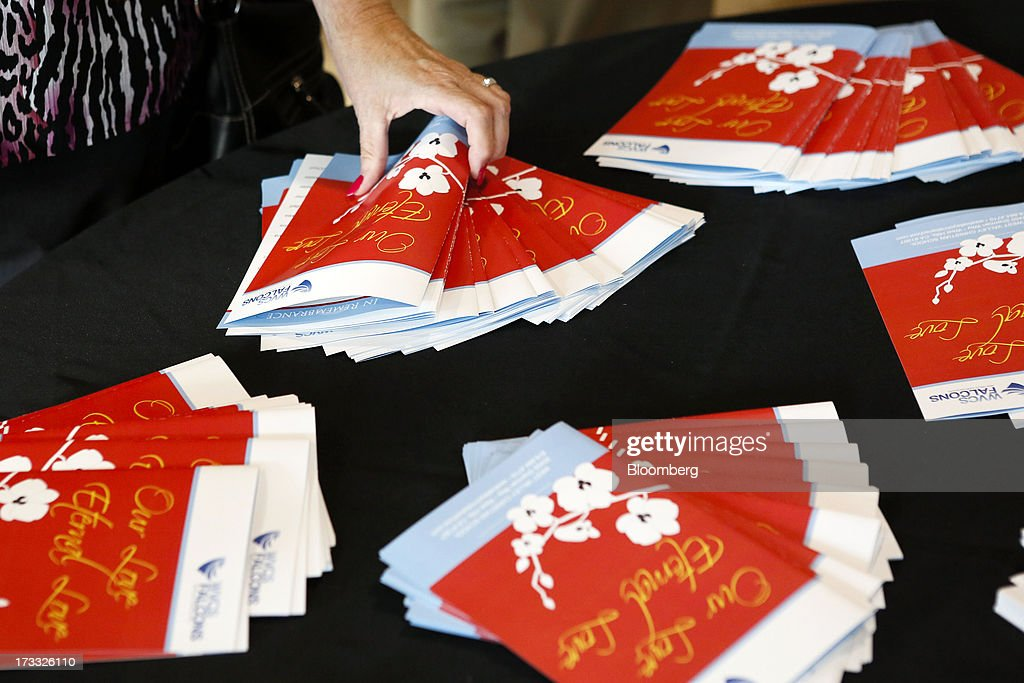 Community members pick up programs for a memorial service for Asiana Airlines Flight 214 crash victims Ye Mengyuan and Wang Linjia at the West Valley...