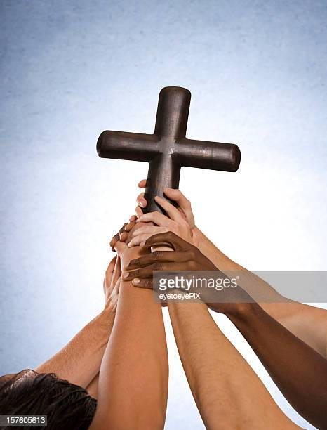 Community of Hands holding cross together