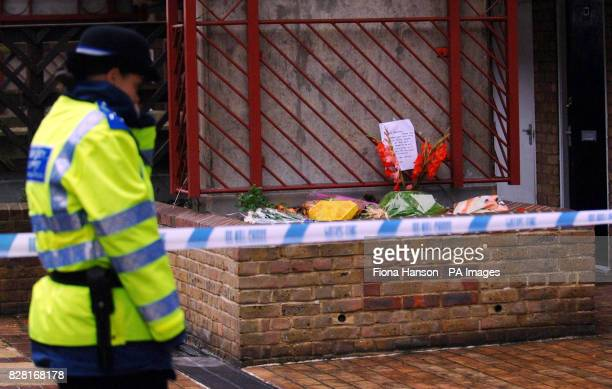 A community support officer walks by a police line and floral tributes on the Milford Towers estate in Catford south London Friday September 30 where...