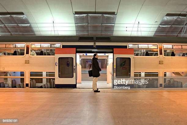 A commuter and passengers wait as an RER train stands at the platform in Paris France on Thursday Jan 29 2009 Frances rail network airports and...