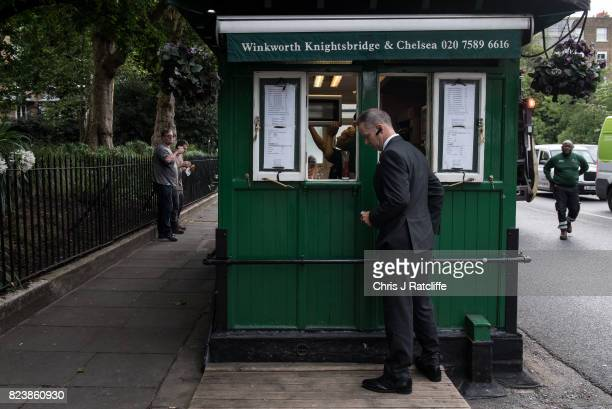 A commuter buys a coffee from the Pont Steet Cabmen Shelter as two workmen eat their recently purchase breakfasts and a refuse worker approaches to...