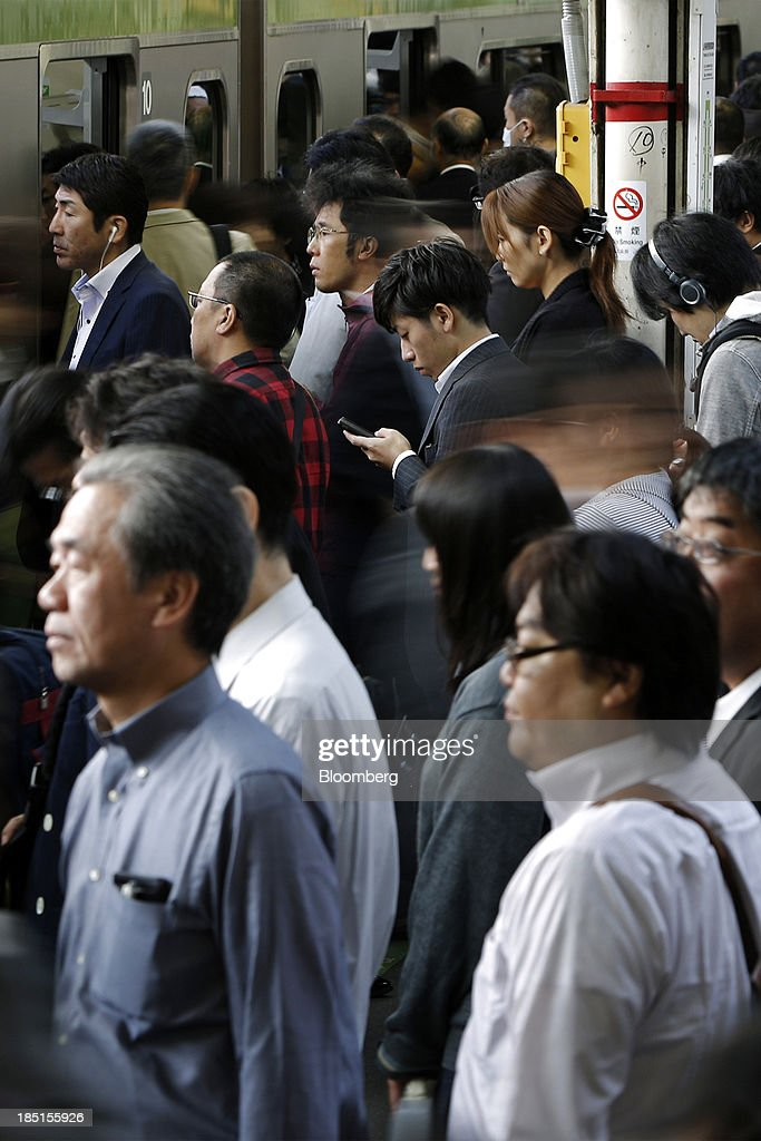 A commuter, center right, stands on a platform using a mobile device while others board a train at a station in Tokyo, Japan, on Thursday, Oct. 17, 2013. Asian stocks rose, sending the benchmark index to a five-month high, while the regions bond risk fell and emerging-market currencies strengthened after U.S. lawmakers voted to raise the nations debt limit. Photographer: Kiyoshi Ota/Bloomberg via Getty Images