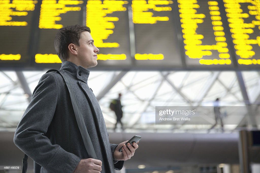 Commuter checks arrivals / depatures board