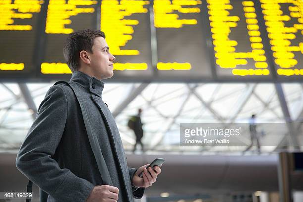 Commuter checks arrivals / depatures board