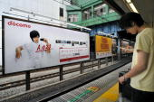 A commuter checks his mobile phone in front of billboard advertising Japanese mobile operator NTT DoCoMo on the Japan Railways aboveground commuter...