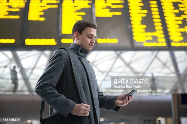 Commuter checks mobile in departure lounge