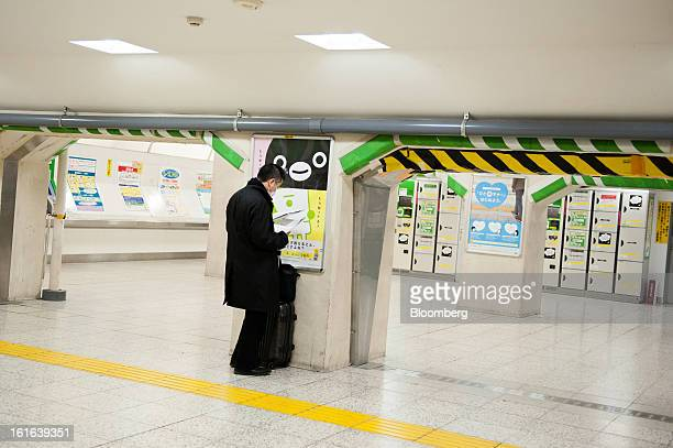 A commuter checks papers as he stands with luggage inside Ueno Station in Tokyo Japan on Wednesday Feb 13 2013 Japan's economy unexpectedly shrank...