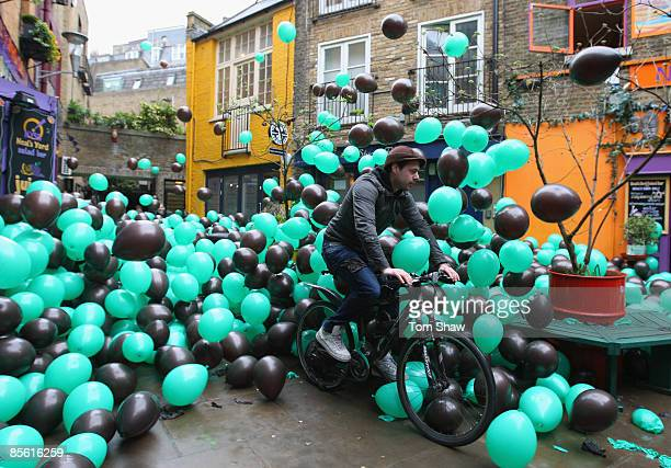 A commuter cycles through London's iconic Neal's Yard under a sea of 10000 balloons as Aero recreates the new 'Feel the Bubbles' advert in Covent...