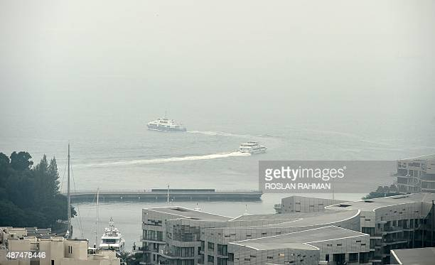 Commuter ferries leave the harbour front terminal as they head to the Indonesian Riau island of Batam across the haze shrouded strait of Singapore on...