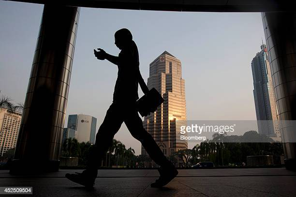 A commuter holding a mobile phone walks past the Public Bank Bhd headquarters building center in Kuala Lumpur Malaysia on Monday July 21 2014...