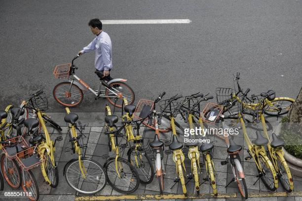 A commuter holds a Mobike bicycle near parked Ofo Inc and Mobike bikes on a sidewalk in Shanghai China on Thursday May 25 2017 In China...