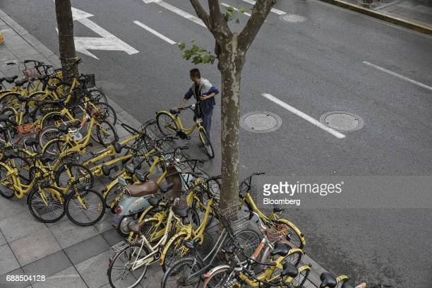 A commuter holds an Ofo Inc bicycle near and parked Ofo and Mobike bikes on a sidewalk in Shanghai China on Thursday May 25 2017 In China...