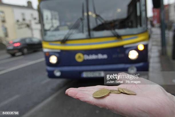 A commuter holds change to purchase a ticket on Dublin Bus at a bus stop in city centre Dublin Ireland as it emerged that prices are to increase