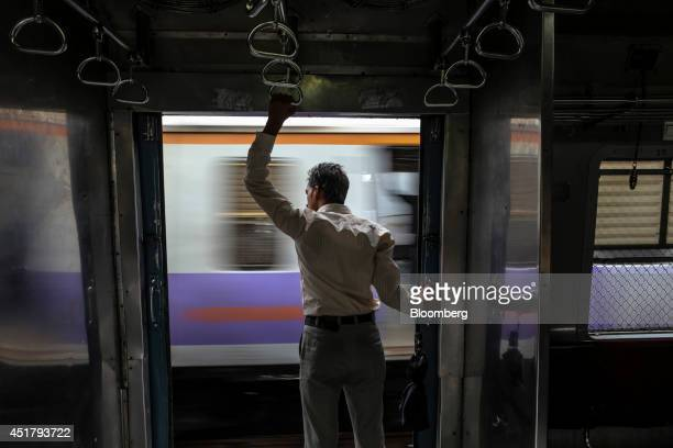 A commuter holds on to a handle as he stands in the doorway of a train while another train passes in Mumbai India on Friday July 4 2014 Indian...