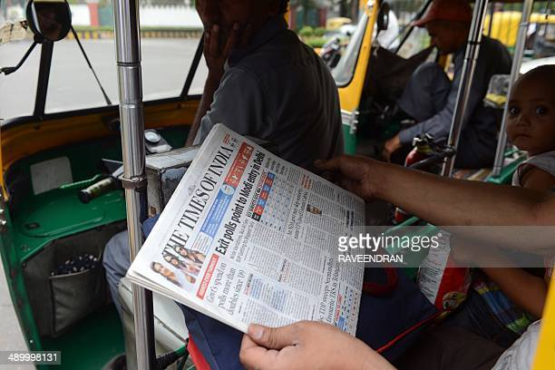 A commuter in an autorickshaw holds up a copy of an Englishlanguage Indian newspaper with the headlines on exit polls showing opposition Bharatiya...