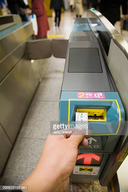 Commuter inserting a ticket into the subway turnstile, close up of hand