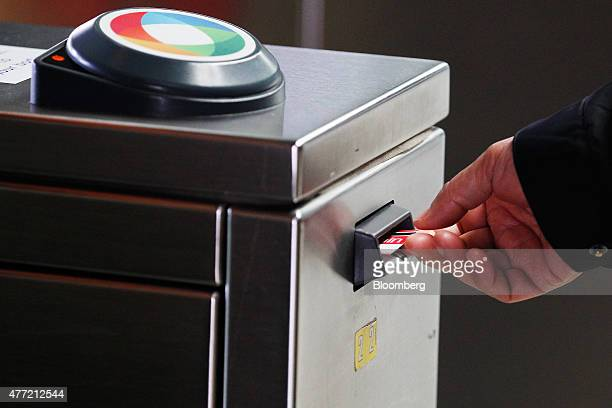 A commuter inserts a train ticket into a ticketing gate at Central Station in Sydney Australia on Tuesday June 9 2015 Australian wages fell in the...