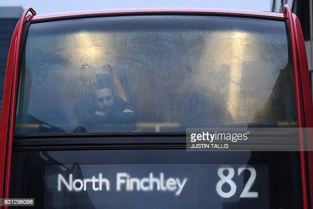 A commuter is seen through the window of a bus at a bus stop near Victoria station in central London on January 9 2017 A strike on the London...