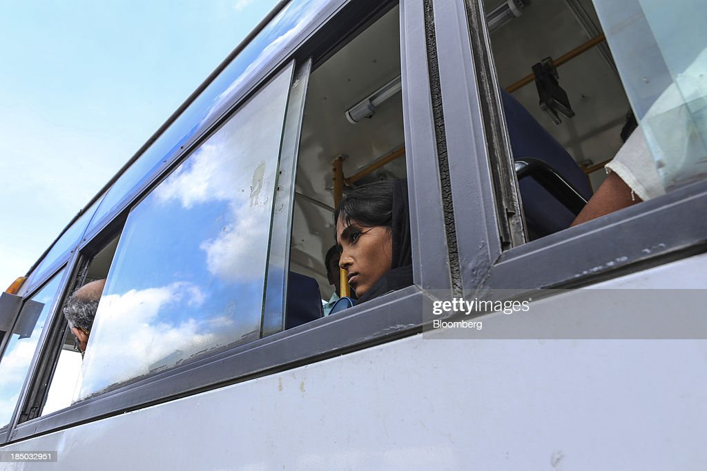 A commuter look out of a bus window as she sits waiting at a station in Bangalore, India, on Saturday, Oct. 12, 2013. Reserve Bank of India Governor Raghuram Rajan has turned the rupee from a pariah to the worlds favorite currency after just a month in office as he intensifies efforts to quell inflation and lure capital. Photographer: Dhiraj Singh/Bloomberg via Getty Images