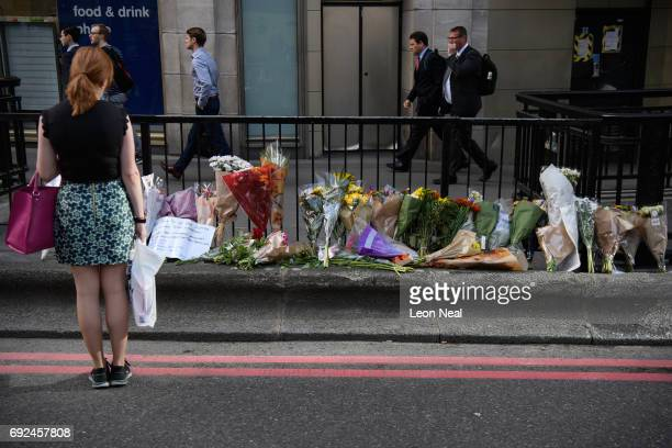 A commuter looks at some of the floral tributes on London Bridge after it was reopened following the June 3rd terror attack on June 5 2017 in London...