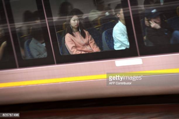 A commuter looks out of a train window as it speeds towards Sydney's Central Station on August 3 2017 / AFP PHOTO / William WEST