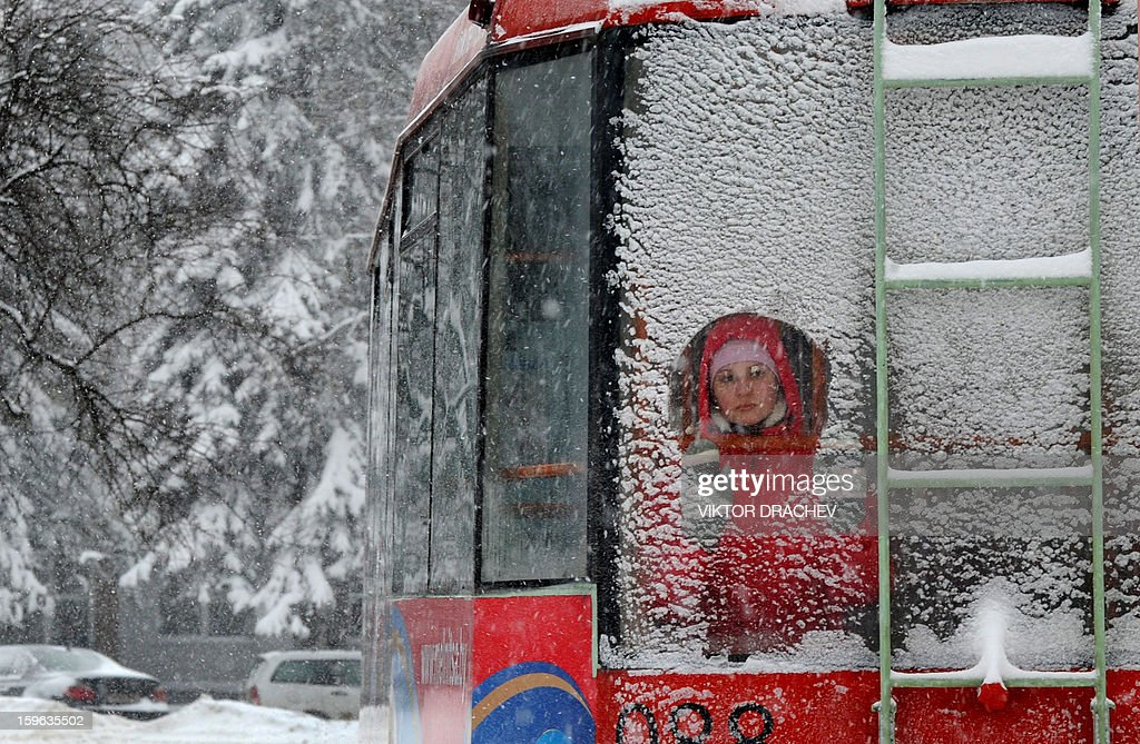 A commuter looks through a snow covered window of a tram in the Belarus capital Minsk, on January 17, 2013. Snow fell today across Minsk as the temperatures dropped to -6 C (21 F). AFP PHOTO / VIKTOR DRACHEV