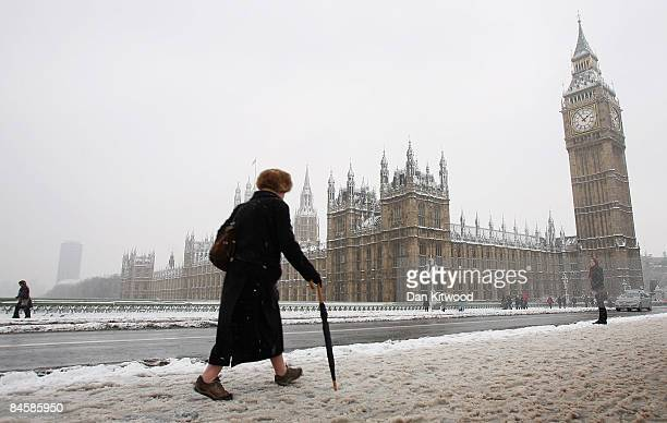 A commuter makes her way across Westminster Bridge as the heavy snow that fell overnight starts to melt on February 2 2009 in London England Heavy...