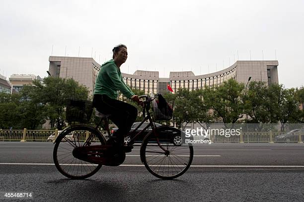 A commuter on a bicycle rides past the People's Bank Of China headquarters in the financial district of Beijing China on Friday Sept 12 2014 Chinese...