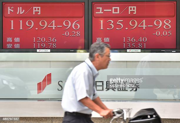 A commuter on bicycle rides in front of boards showing numbers of the yen rate against the US dollar and the euro in Tokyo on August 27 2015 Tokyo...