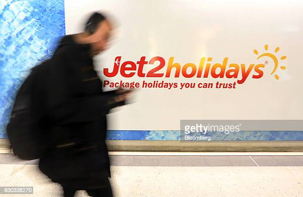 A commuter passes a poster advertising Jet2com holidays at Liverpool Street railway and underground station in London UK on Wednesday Dec 21 2016 The...