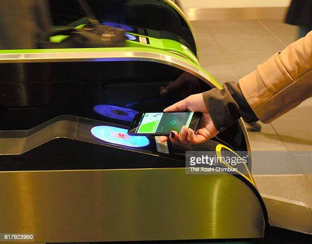 A commuter passes her iPhone 7 over a card reader to walk through a ticket gate as Apple Pay launches in Japan on October 25 2016 in Tokyo Japan