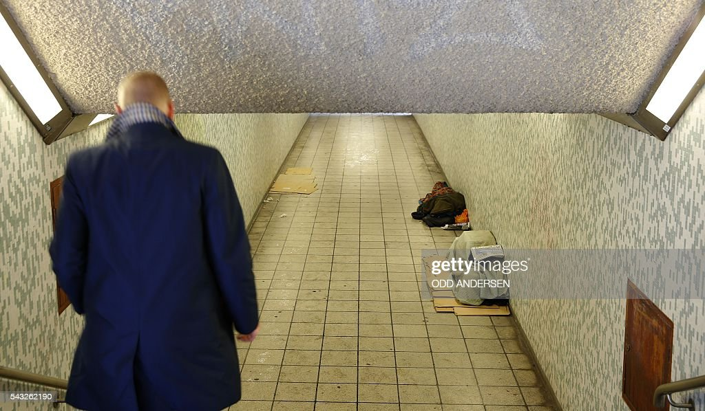 A commuter passes homeless people as the sleep in an underpass in central London on June 27, 2016. Britain should only trigger Article 50 to leave the EU when it has a 'clear view' of how its future in the bloc looks, finance minister George Osborne said Monday following last week's shock referendum. / AFP / ODD