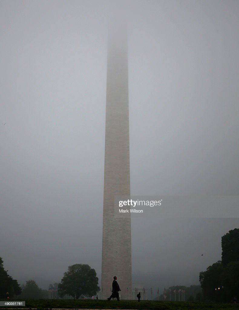 A commuter passes in front of the newly reopended Washington Monument as it is shrouded in fog on May 14, 2014 in Washington, DC. The Washington Monument was reopened after it has been closed for a restoration due to the damages caused by a 5.8-magnitude earthquake that struck the Washington, DC, area on August 23, 2011.