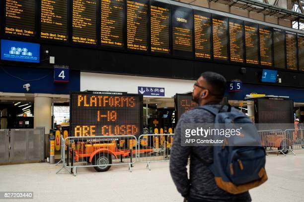 A commuter passes signs alerting passengers to the closure of platforms 110 at London Waterloo rail station in central London on August 7 as Network...