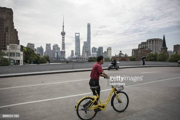 A commuter pushes an Ofo Inc bicycle along a sidewalk in Shanghai China on Thursday May 25 2017 In China abicyclesharingphenomenon is changing the...