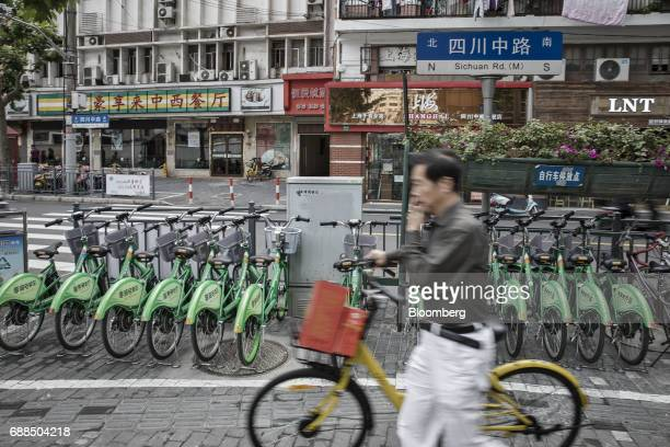 A commuter pushes an Ofo Inc bicycle past parked Xiangqi Chuxing electric bikes on a sidewalk in Shanghai China on Thursday May 25 2017 In China...