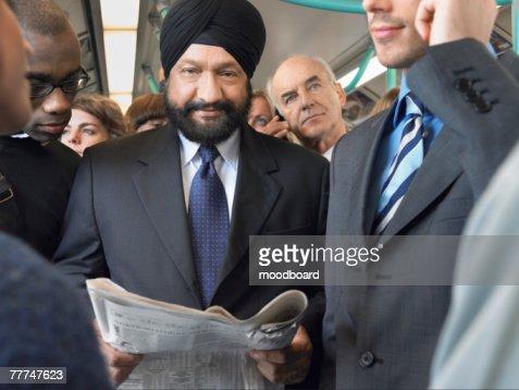 Commuter Reading Businessmans Paper on Train