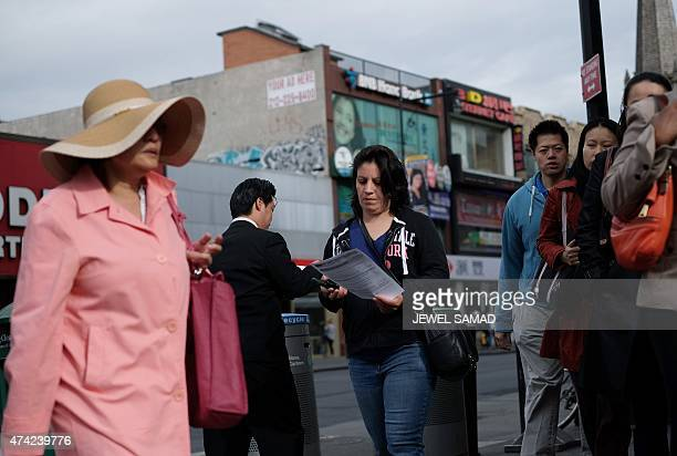 A commuter reads a flyer about health concerns labor practices regulations and wages at nail salons she received from a volunteer outside a subway...