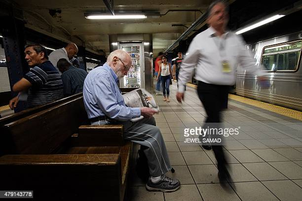 A commuter reads a newspaper as he waits for a train in a subway station in New York on July 1 2015 AFP PHOTO/JEWEL SAMAD