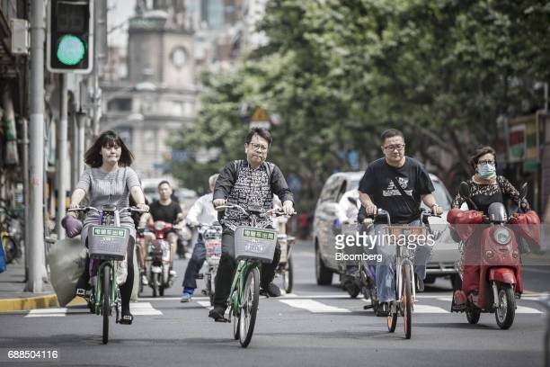 Commuter ride Mobike second right and other bicycles through an intersection in Shanghai China on Thursday May 25 2017 In China...