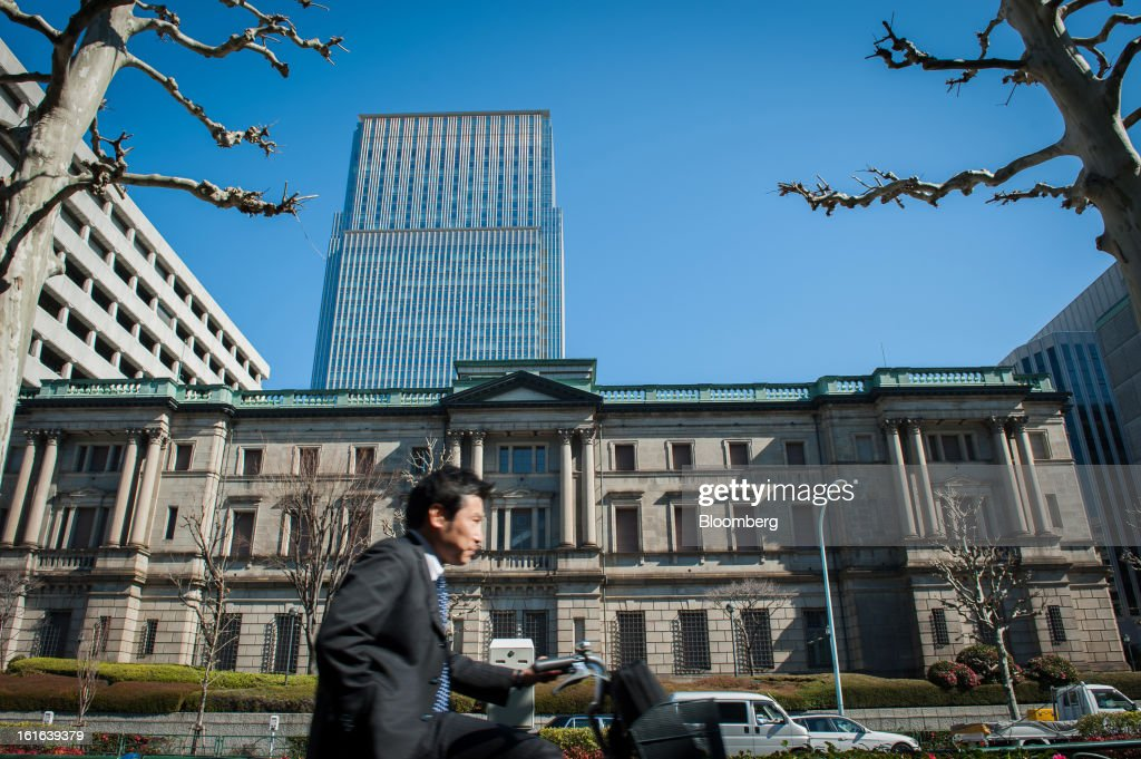 A commuter rides a bicycle past the Bank of Japan headquarters in Tokyo, Japan, on Wednesday, Feb. 13, 2013. Japan's economy unexpectedly shrank last quarter as falling exports and a business investment slump outweighed improved consumption, highlighting the challenge facing Prime Minister Shinzo Abe as he seeks to end deflation. Photographer: Noriko Hayashi/Bloomberg via Getty Images