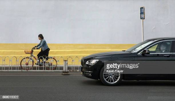 A commuter rides a bike share beside a luxury car during rush hour on April 6 2017 in Beijing China The popularity of bike shares has exploded in the...