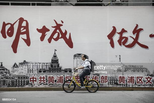 A commuter rides an Ofo Inc bicycle along a sidewalk in Shanghai China on Thursday May 25 2017 In China abicyclesharingphenomenon is changing the...