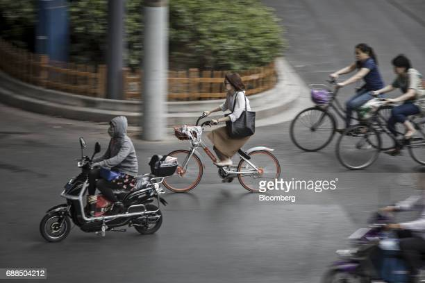 A commuter rides on a Mobike bicycle center along a street in Shanghai China on Thursday May 25 2017 In China a bicyclesharing phenomenon is changing...