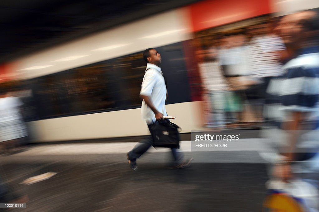 A commuter runs on a platform before the departure of a RER regional train at the Denfert-Rochereau station in Paris on June 24, 2010 as a mass strike against the French government's plan to raise the retirement age disrupted transport. The bill raising the retirement age from 60 to 62 is due to be voted on in September.
