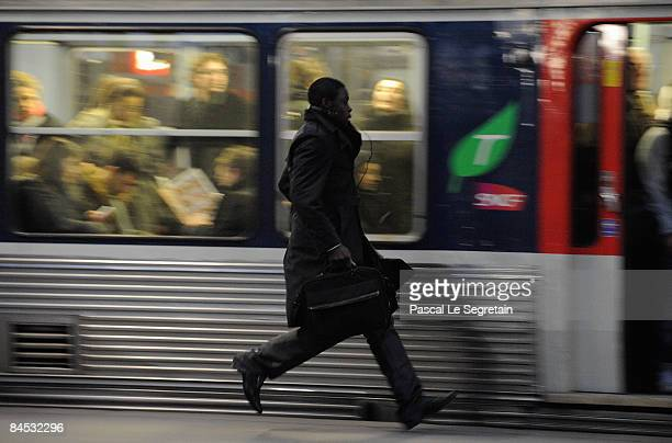 A commuter runs on a platform to catch his train at Paris Saint Lazare railway station on January 29 2009 in Paris France Commuters were disrupted...